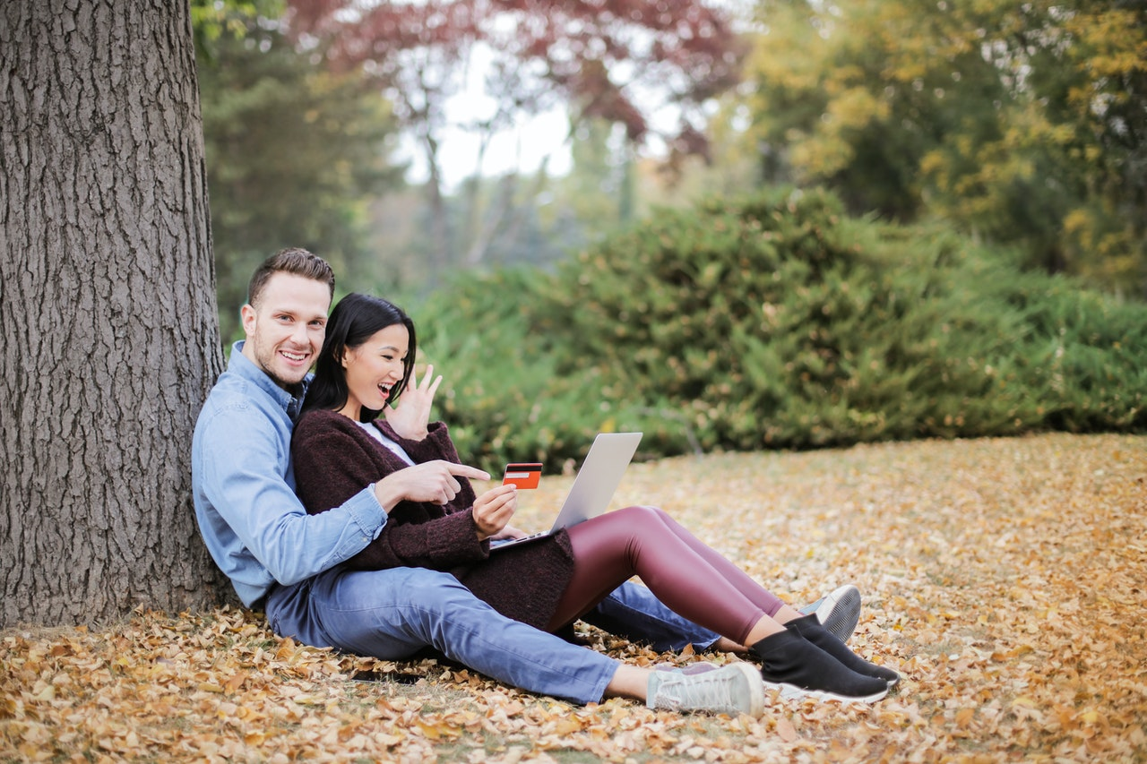 Couple sitting in the park with credit card